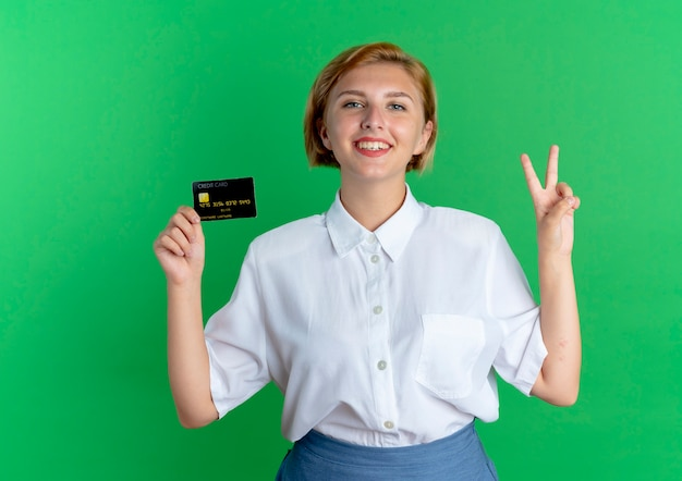 Jong glimlachend blond russisch meisje houdt creditcard en gebaren overwinning handteken