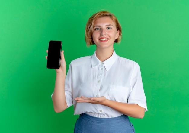 Jong glimlachend blond russisch meisje houdt en wijst met hand op telefoon die op groene achtergrond met exemplaarruimte wordt geïsoleerd