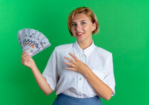 Jong glimlachend blond russisch meisje houdt geld en gebaren vier met vingers