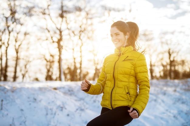 Jong glimlachend en geconcentreerd sportief actief meisje met een paardenstaart die in wintersportkleding de sneeuwaard in de ochtend verwarmen.