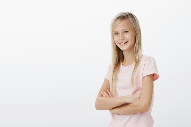 Jong glimlachend jong geitje dat gelukkig kijkt. kleine vrouw die zich over witte vrolijke muur bevindt