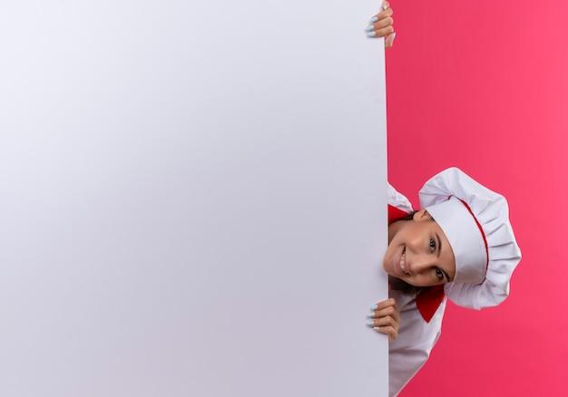 Jong glimlachend kaukasisch kokmeisje in eenvormige chef-kok bevindt zich achter witte muur op roze met exemplaarruimte