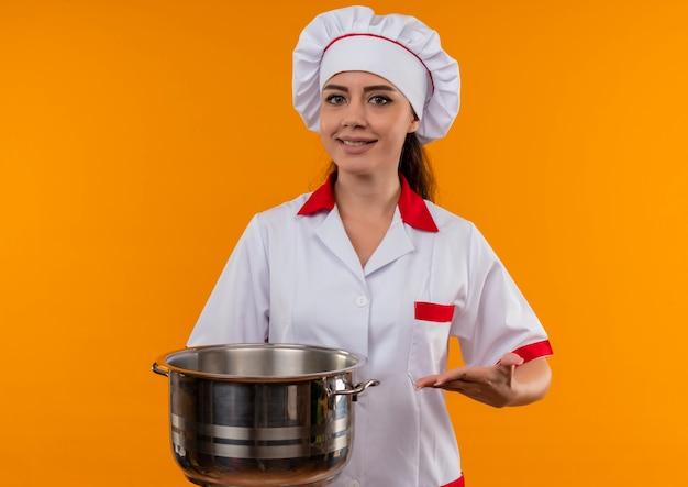 Jong glimlachend kaukasisch kokmeisje in eenvormige chef-kok houdt en punten met hand bij pot die op oranje muur met exemplaarruimte wordt geïsoleerd