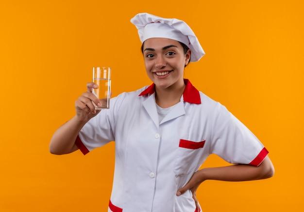 Jong glimlachend kaukasisch kokmeisje in eenvormige chef-kok houdt glas water en legt hand op taille die op oranje muur wordt geïsoleerd