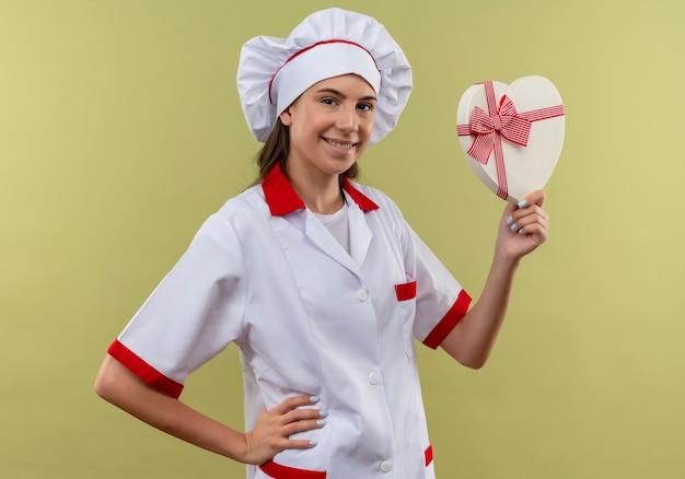 Jong glimlachend kaukasisch kokmeisje in eenvormige chef-kok houdt hartvormdoos en legt hand op taille die op groene ruimte met exemplaarruimte wordt geïsoleerd