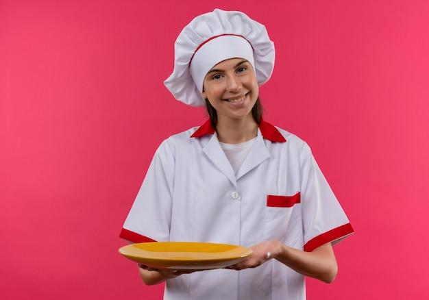 Jong glimlachend kaukasisch kokmeisje in eenvormige chef-kok houdt plaat en bekijkt camera op roze met exemplaarruimte