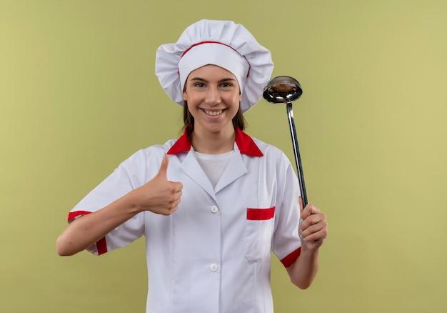 Jong glimlachend kaukasisch kokmeisje in eenvormige chef-kok houdt pollepel en duimen omhoog geïsoleerd op groene achtergrond met exemplaarruimte