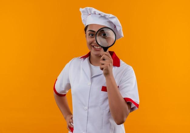 Jong glimlachend kaukasisch kokmeisje in eenvormige chef-kok kijkt door vergrootglas of loupe geïsoleerd op oranje muur