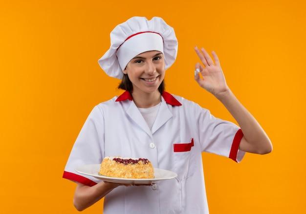 Jong glimlachend kaukasisch kokmeisje in uniform chef-kok houdt cake op plaat en gebaren ok handteken dat op oranje achtergrond met exemplaarruimte wordt geïsoleerd