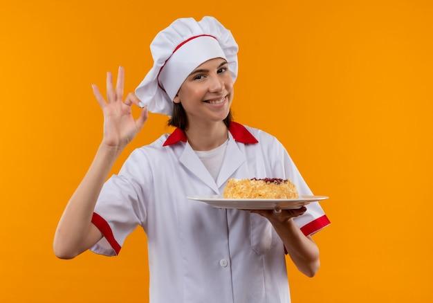 Jong glimlachend kaukasisch kokmeisje in uniform chef-kok houdt cake op plaat en gebaren ok handteken dat op oranje ruimte met exemplaarruimte wordt geïsoleerd