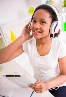 Jong glimlachend mulatschoolmeisje dat aan de muziek luistert.
