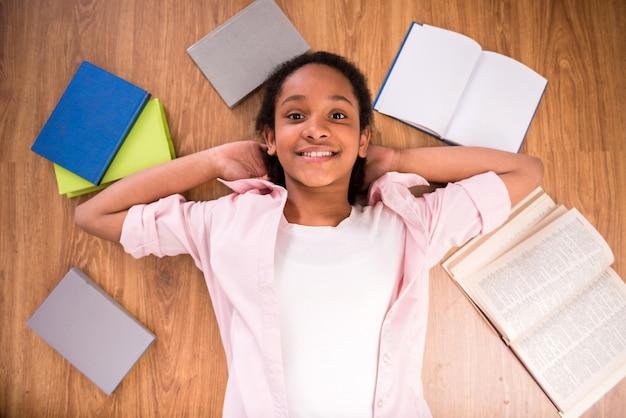 Jong glimlachend mulatschoolmeisje dat op de vloer legt.