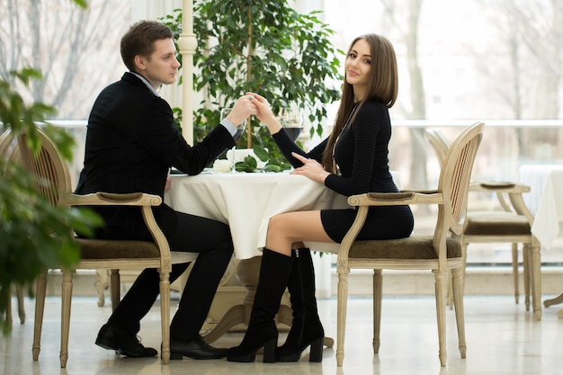 Jong glimlachend paar dat bij een lijst in een restaurant romancing