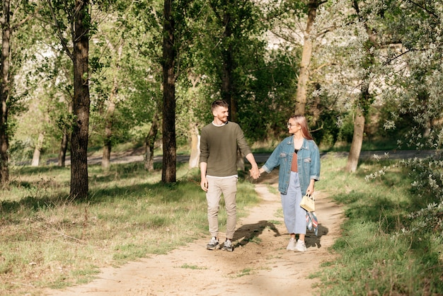 Jong glimlachend paar dat in het park geniet van.