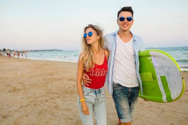 Jong glimlachend paar dat pret op strand heeft die met surfplank loopt