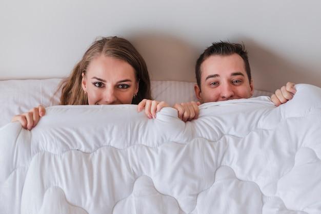 Jong glimlachend paar die op bed liggen en uit van dekbed piepen