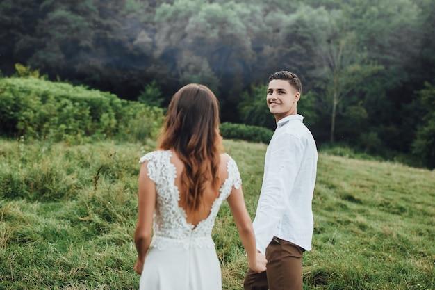 Jong glimlachend paar die op perfect landschap houden