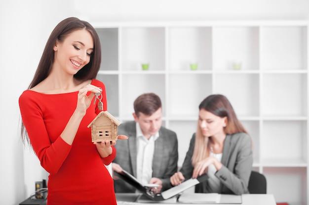 Jong glimlachend paar ongeveer om een huishuurovereenkomst te ondertekenen, gelukkig om nieuw appartement te kopen