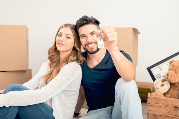 Jong glimlachend stel dat hun nieuwe huissleutels, onroerend goed en verhuisconcept vasthoudt