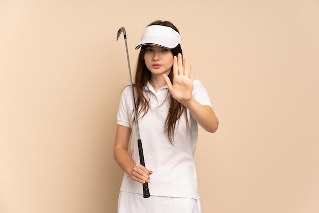 Jong golfer meisje geïsoleerd op beige stop gebaar maken
