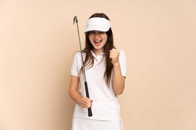 Jong golfer meisje geïsoleerd op beige vieren een overwinning in winnaarspositie