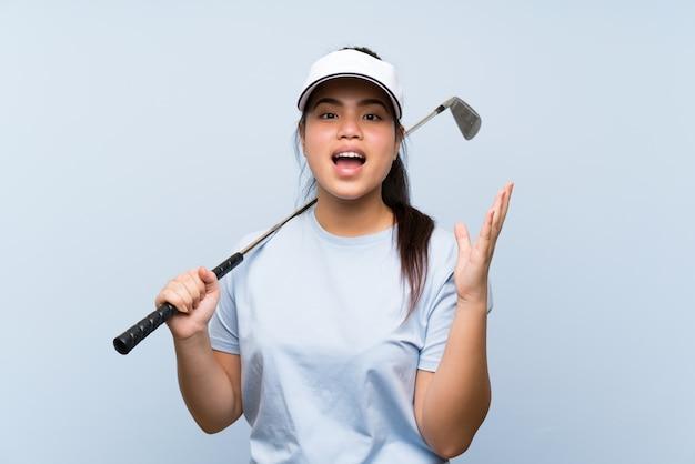 Jong golfspeler aziatisch meisje met geschokte gelaatsuitdrukking