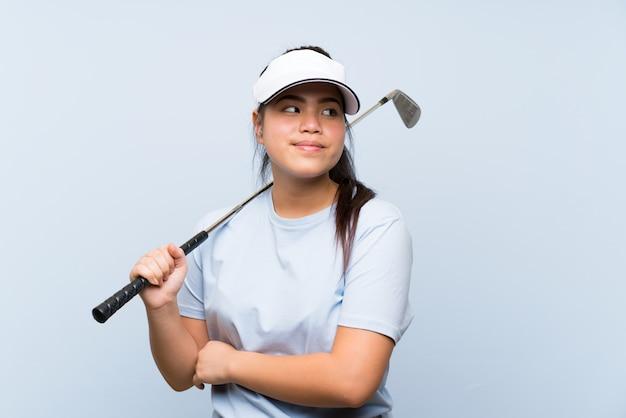Jong golfspeler aziatisch meisje over geïsoleerde blauwe muur die twijfelsgebaar maken terwijl het opheffen van de schouders