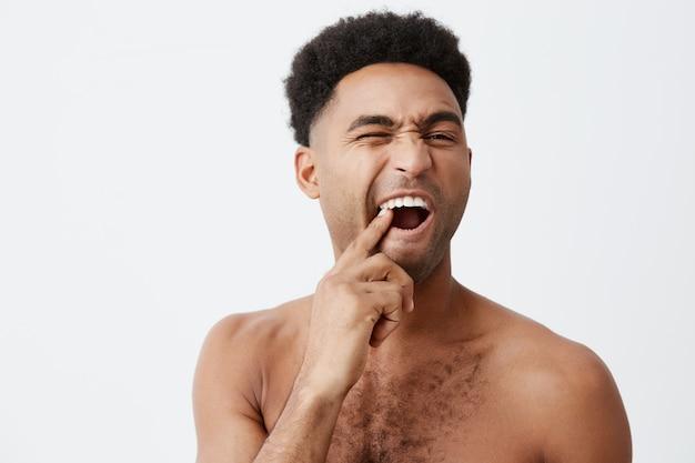 Jong grappig knap afro amerikaans mannetje met krullend haar zonder kleren die tanden plukken die spiegel met gemiddelde uitdrukking bekijken die bad in ochtend nemen.