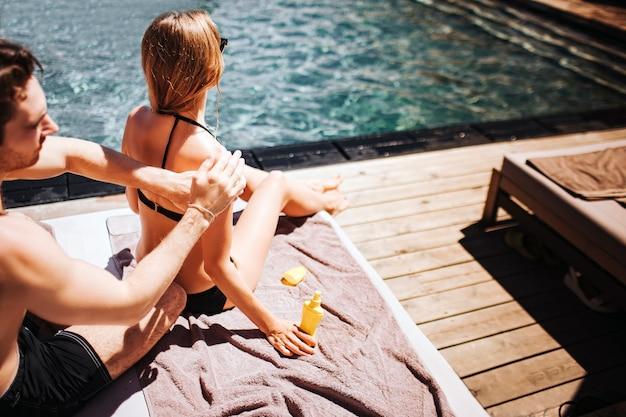 Jong heet paar dat bij zwembad rust. snijd het beeld van een man die wat zonnebrandcrème op de huid van het meisje aanbrengt