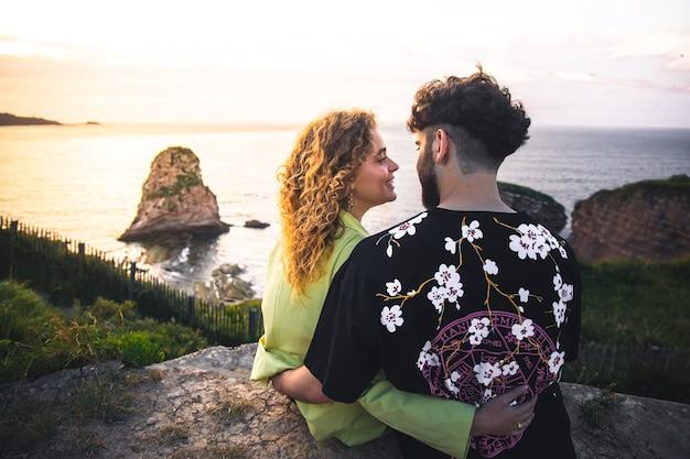 Jong heteroseksueel paar omhelzen elkaar op de top van een klif in de buurt van de oceaan.