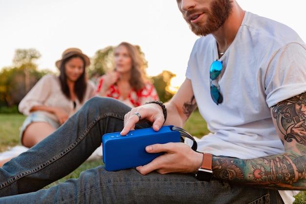 Jong hipster-gezelschap van vrienden die samen plezier hebben in het park, glimlachend luisterend naar muziek op draadloze luidspreker