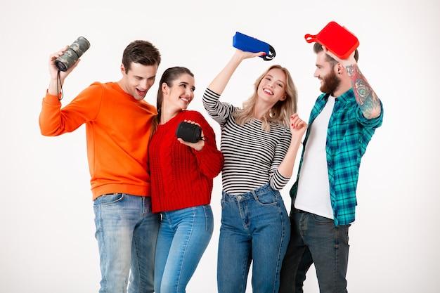 Jong hipster-gezelschap van vrienden die samen plezier hebben terwijl ze naar muziek luisteren op draadloze luidsprekers