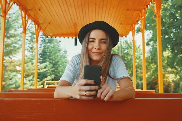 Jong hipstermeisje in trendy smartphone van de hoedenholding in handen