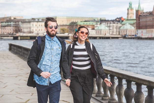 Jong hipsterpaar die hand in hand in stockholm lopen