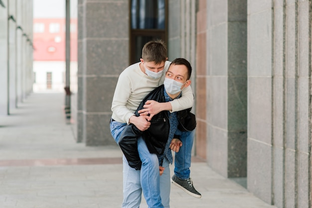 Jong homopaar dat medisch masker draagt dat bij de stad koestert.