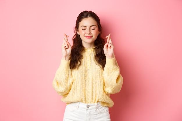 Jong hoopvol meisje met geloof, wensdroom die uitkomt, kruis vingers voor geluk en sluit ogen, lachend tijdens het bidden, staande over roze muur.