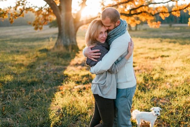 Jong houdend van paar dat op de herfstgebied bij zonsondergang koestert