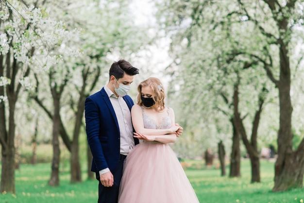 Jong houdend van paar die gezichtsmaskers op hun huwelijksdag dragen