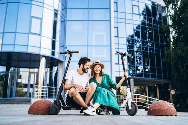 Jong houdend van paar ontspannende zitting dichtbij een modern glasgebouw met hun elektrische autopedden. wandelingen in de grote stad
