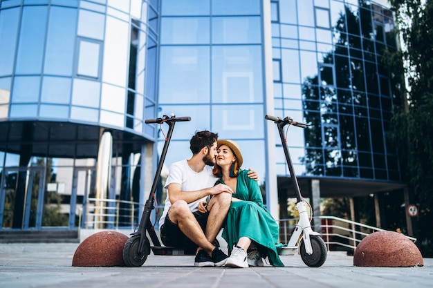 Jong houdend van paar ontspannende zitting dichtbij een modern glasgebouw met hun elektrische autopedden.