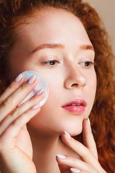 Jong huidverzorgingsconcept aantrekkelijk tienermeisje met lang rood krullend haar wrijft over haar gezicht
