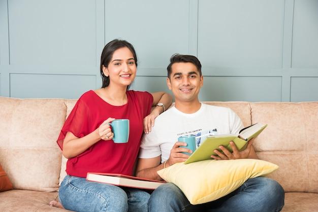 Jong indiaas aziatisch stel dat boeken leest terwijl ze thuis op de bank zitten, moderne leefruimte