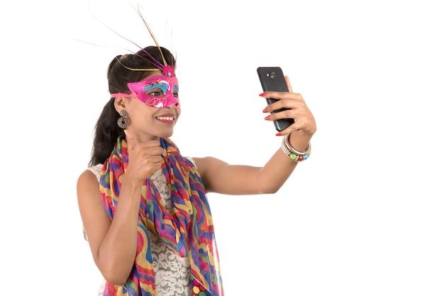Jong indisch meisje met behulp van een mobiele telefoon of smartphone geïsoleerd op een witte achtergrond