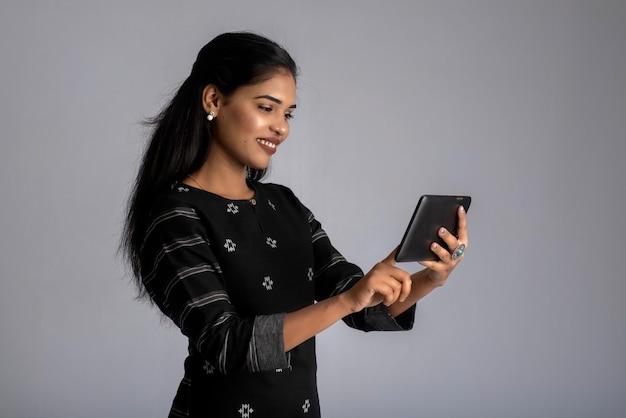 Jong indisch meisje met behulp van een mobiele telefoon of smartphone op grijs