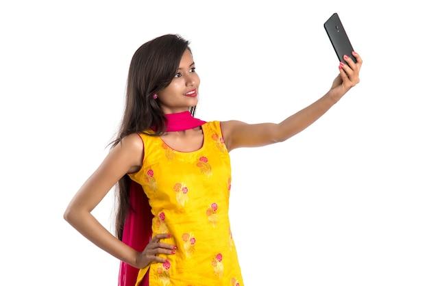 Jong indisch meisje met behulp van een tablet, mobiele telefoon of smartphone geïsoleerd op een wit