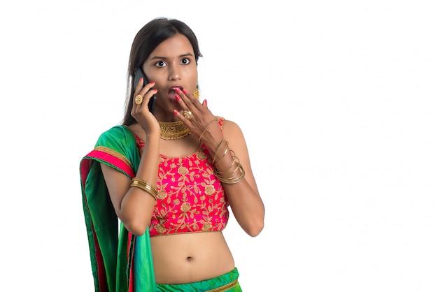 Jong indisch traditioneel meisje die een mobiele telefoon of een smartphone gebruiken die op een wit wordt geïsoleerd