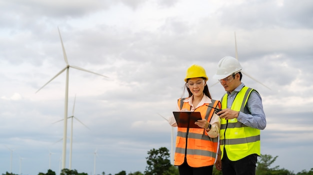 Jong ingenieursteam dat met rapport in klembord tegen windturbinepark werkt