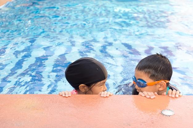 Jong jongen en meisje die in pool zwemmen.