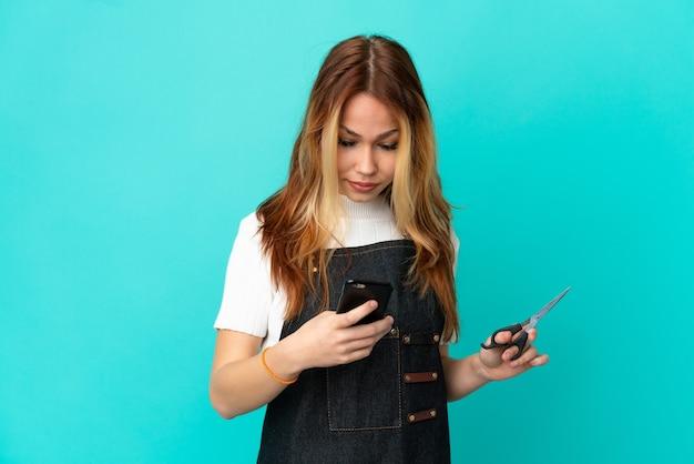 Jong kappersmeisje dat over geïsoleerde blauwe achtergrond een bericht met mobiel verzendt