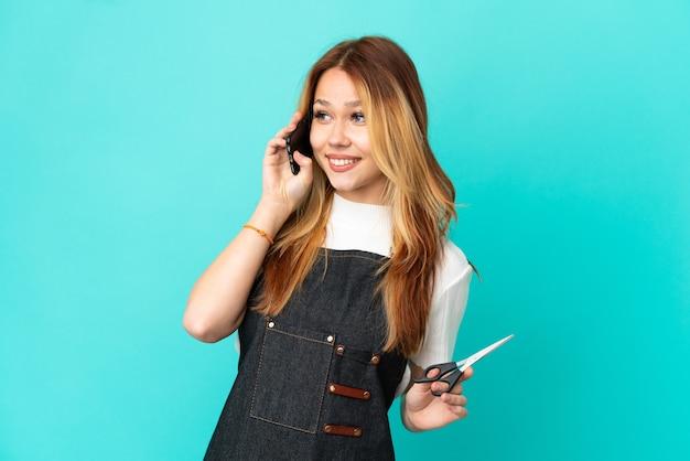 Jong kappersmeisje over geïsoleerde blauwe achtergrond die een gesprek met de mobiele telefoon met iemand houdt